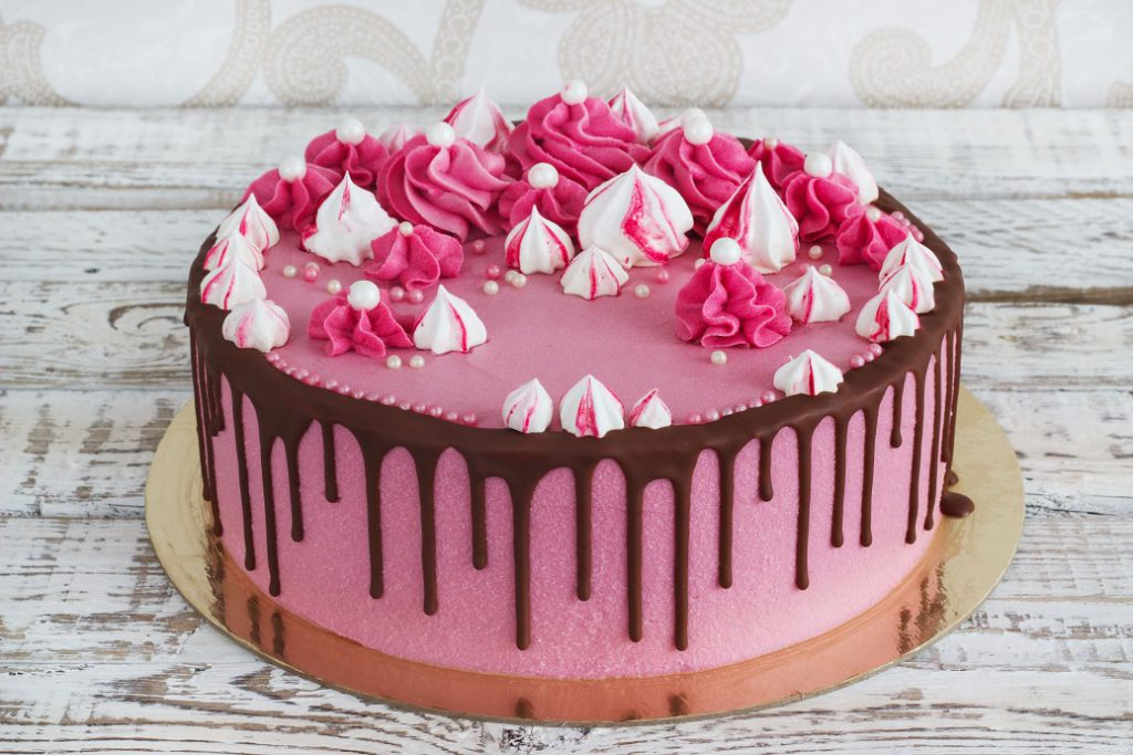 Pink cream cake meringues with smudges of chocolate on a white wooden background